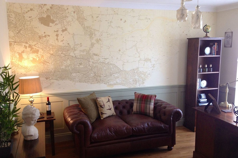 Sepia style vintage map wallpaper in the home study with leather sofa and bookcase