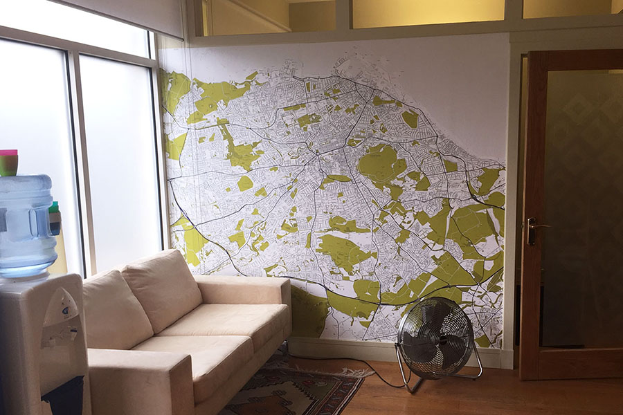 Custom map wallpaper mural in waiting area with sofa and water dispenser