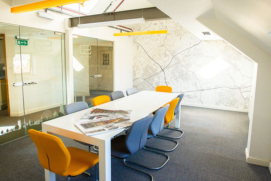 Architect's office with map wallpaper and orange chairs