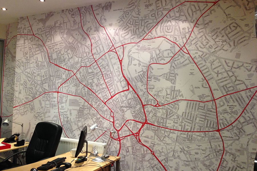 Red and grey custom map wallpaper in office with desk and chair
