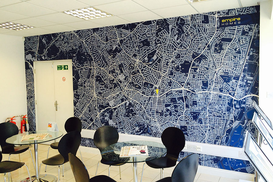 Blue and white map wallpaper in estate agent with tables and chairs