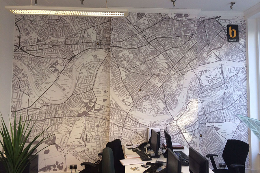 Black and white custom map area wallpaper in office with desk and plants