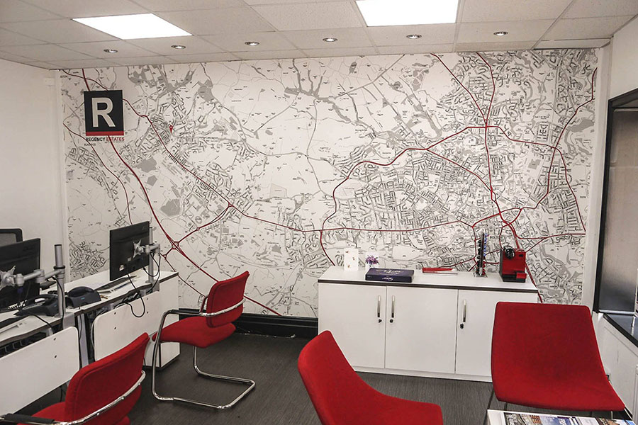 Red and white map wallpaper in estate agency office with red chairs